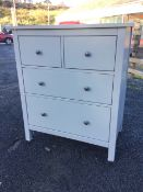 A modern painted chest of two short and two long graduated drawers mounted with metal knobs,