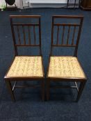 A pair of Edwardian mahogany bedroom chairs, the spindle backs with satinwood banding above