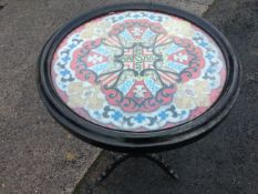 A circular Victorian tray-top beadwork table, the flag style scrolled panel under glass in moulded