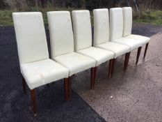 A set of six cream leather upholstered dining chairs, with tall backs above tapering seats, raised