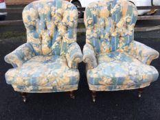 A pair of Victorian style button upholstered armchairs covered in floral linen, having loose