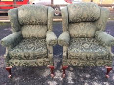 A pair of Queen Anne style upholstered wing armchairs, with padded backs and loose cushions above