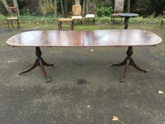 A Georgian style mahogany twin pedestal dining table, the crossbanded top with ebony stringing