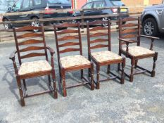 A set of four stained ladderback dining chairs with floral tapestry drop-in upholstered seats,