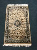 A silk style oriental rug woven with central circular medallion and multi-floral designs on pink
