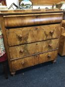 A nineteenth century European mahogany chest of drawers, the rounded moulded top above a cushion
