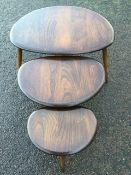 A nest of three 70s Ercol elm pebble design tables, the shaped tops on angled turned legs. (3)