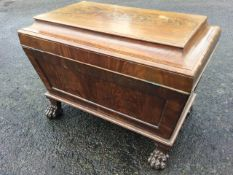 A nineteenth century mahogany cellarette of panelled sarcophagus form, the moulded cover with flat