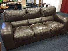 A large leather upholstered three-seater sofa with panelled cushions, raised on block feet. (86in