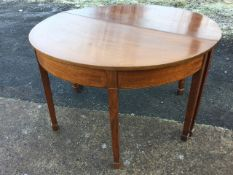 A pair of nineteenth century D shaped mahogany tables forming a circle, the friezes inlaid with