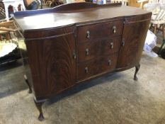 A mahogany sideboard having shaped upstand above rectangular moulded top with three central drawers,