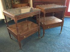 A pair of mahogany tables with plate glass tops framed by raised scalloped galleries above slides,