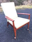 A Danish style armchair with upholstered padded back above a sprung seat with loose cushion, the