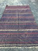 A large Balouch kelim woven with blue, red, cream and orange bands on chocolate brown ground, see