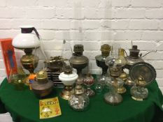 A collection of Victorian brass oil lamps, many with chimneys, together with a book - Discovering