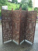 A four-fold oriental carved hardwood screen, with pierced fretwork panels in frames inlaid with