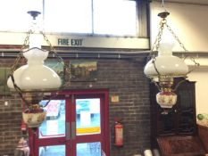 A pair of Victorian style hanging oil lamps, the electric wired lights having ceramic reservoirs