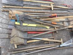 A quantity of garden tools including rakes, forks, shovels, a bolt cutter, a yard brush, hoes, pitch