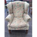 A Georgian style wing armchair with arched back and padded splayed arms above a loose cushion