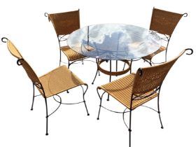 A contemporary circular glass topped conservatory table raised on waisted scrolled legs with
