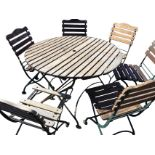 A circular folding garden table with six chairs, the table with slatted top having central hole