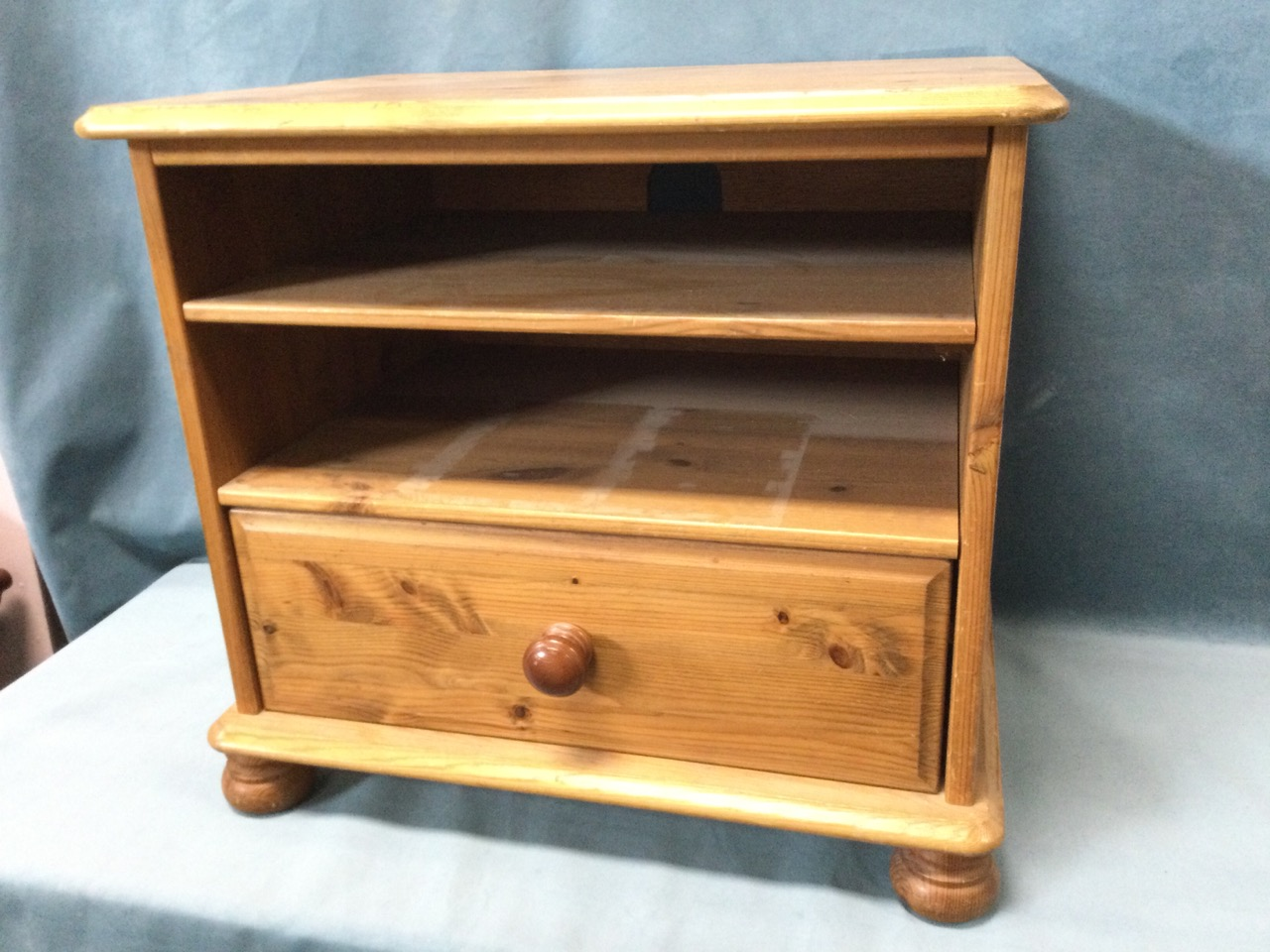 A pine cabinet with moulded top above open shelves and knobbed drawer, raised on bun feet. (22.5in x