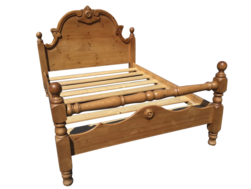 A pine double bed, with carved arched headboard framed by square cornerposts with ball finials,
