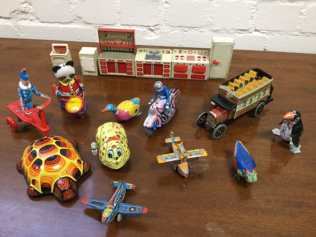 A 1950s childs tinplate kitchen with six freestanding pieces; and eleven tinplate mainly clockwork