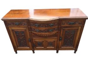 A Victorian carved walnut sideboard, the bowfronted central section with two drawers above a
