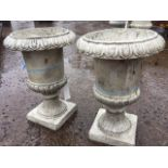 A pair of composition resin garden urns with lozenge moulded rims on fluted tapering bodies, with