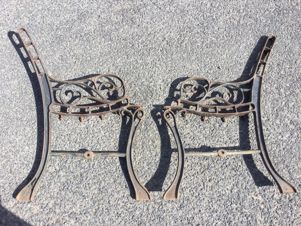 A pair of cast iron bench ends with channelled frames, the arms on pierced scrolled supports, raised