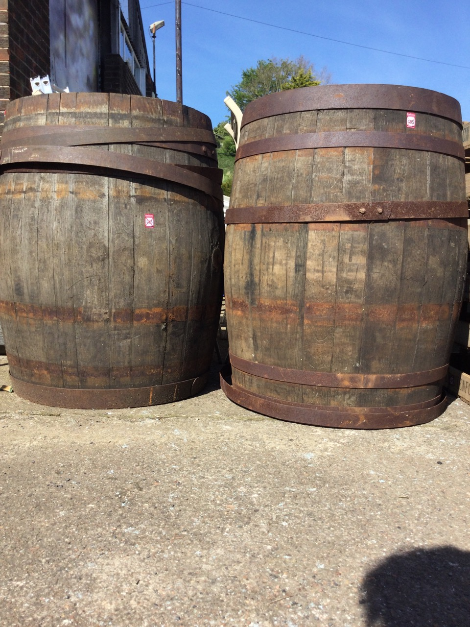 A pair of large oak whiskey barrels, the staves bound by riveted strap bands - some loose. (34.75in) - Image 3 of 3