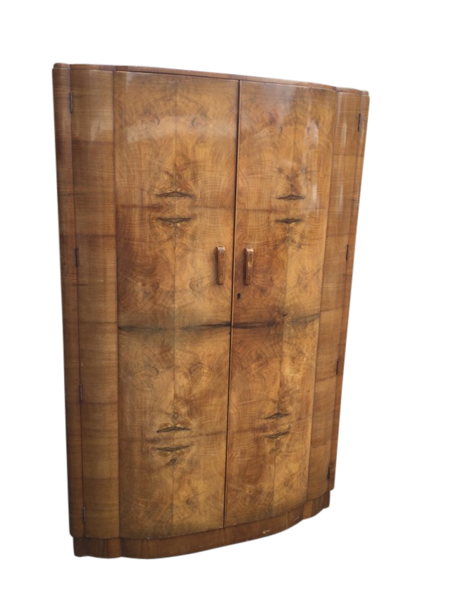 A deco walnut wardrobe of scalloped bowfronted outline having two doors enclosing an interior with