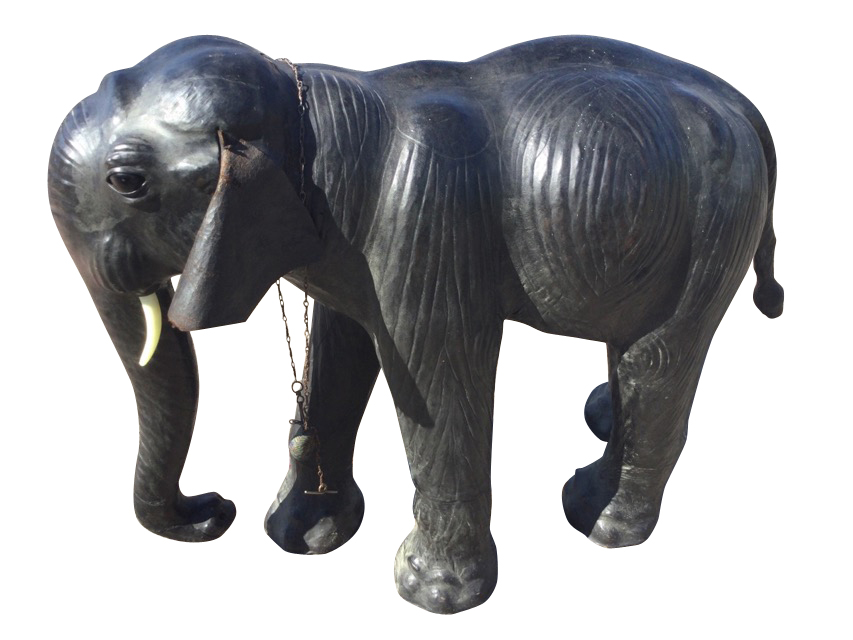 A C20th leather mounted Liberty style elephant, the beast with glass eyes modelled walking with