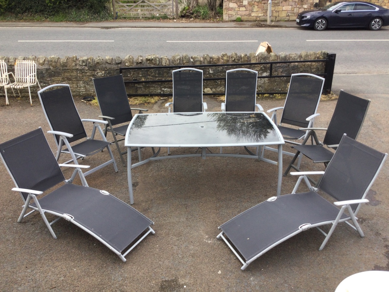 A contemporary rectangular garden table & chair set, the folding chairs with fabric backs & seats