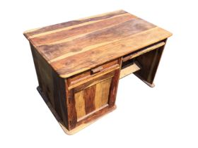 A hardwood desk with rectangular rounded moulded top above a drawer and panelled door cupboard