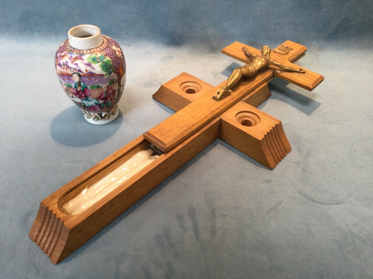 An oak absolution crucifix with sliding case revealing holy water bottle, and a pair of candles to