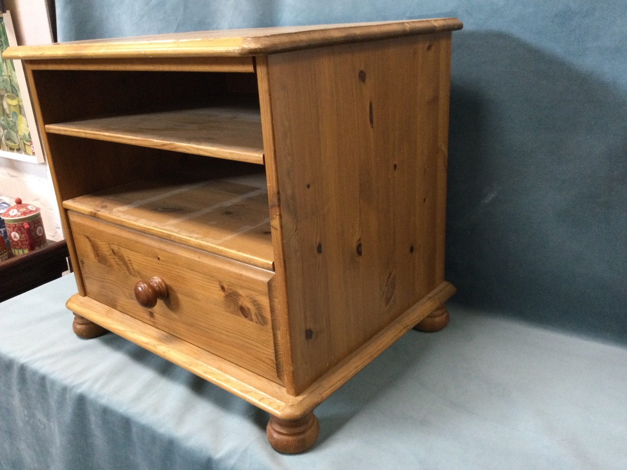 A pine cabinet with moulded top above open shelves and knobbed drawer, raised on bun feet. (22.5in x - Image 3 of 3