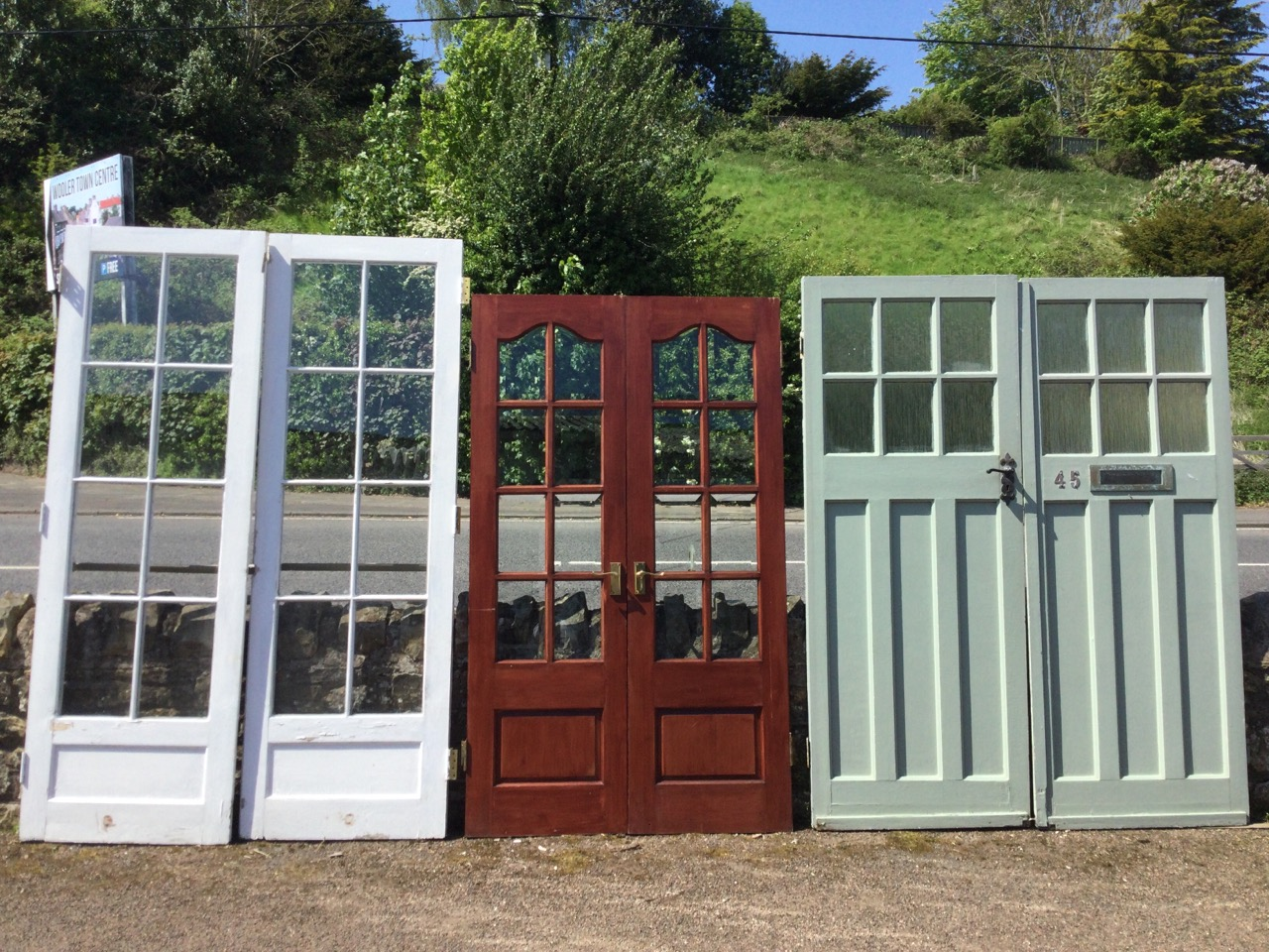 A pair of glazed hardwood patio doors with bevelled glass panes, having arched tops and fielded
