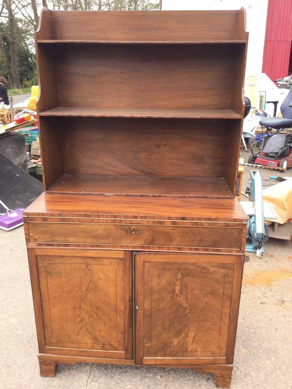 A mahogany secretaire bookcase with open shelves above a turn-over crossbanded desk with baize