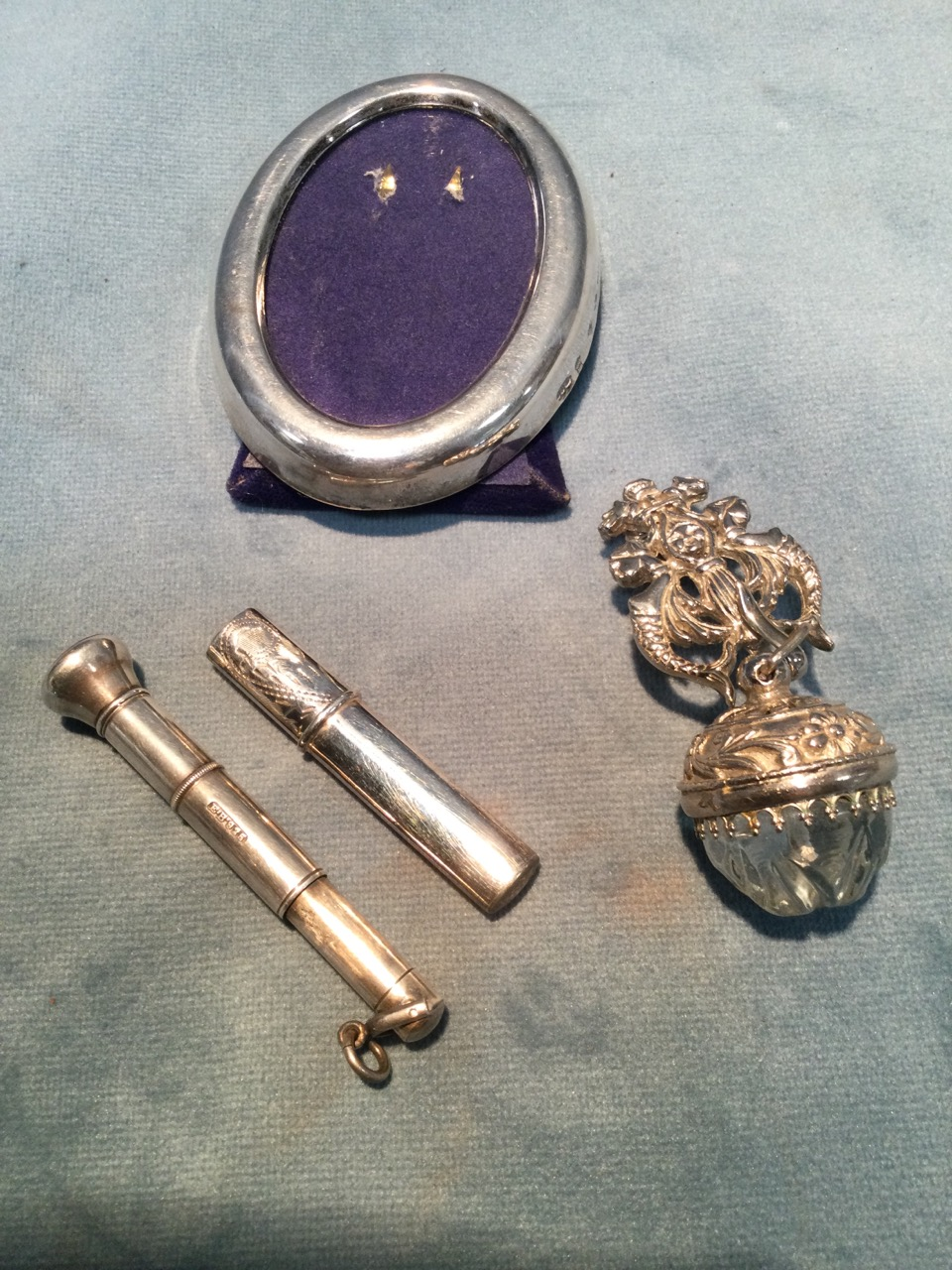 A small oval hallmarked silver photo frame; a telescopic silver cherute holder; a glass ball