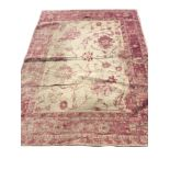 A Egyptian made contemporary rug woven with fawn field of flowers and scrolled tendrils, within a