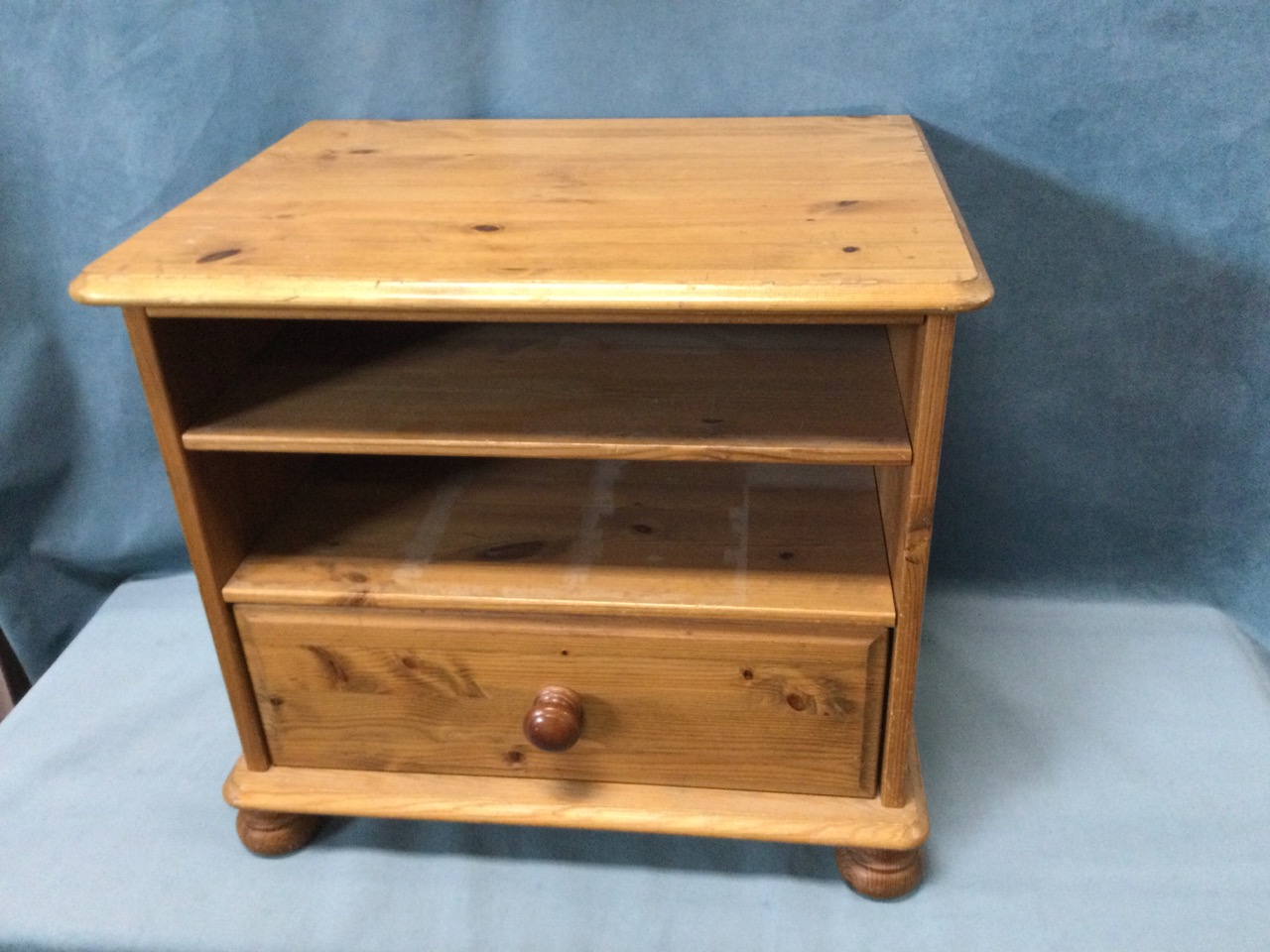 A pine cabinet with moulded top above open shelves and knobbed drawer, raised on bun feet. (22.5in x - Image 2 of 3