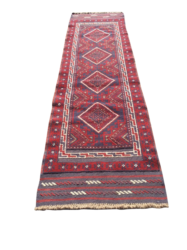 A Turkish runner woven with red field of four diamond shaped medallions with blue hooked borders,
