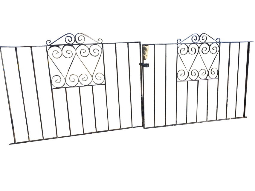 A pair of wrought iron driveway gates with vertical bars in rectangular frames, having scrolled