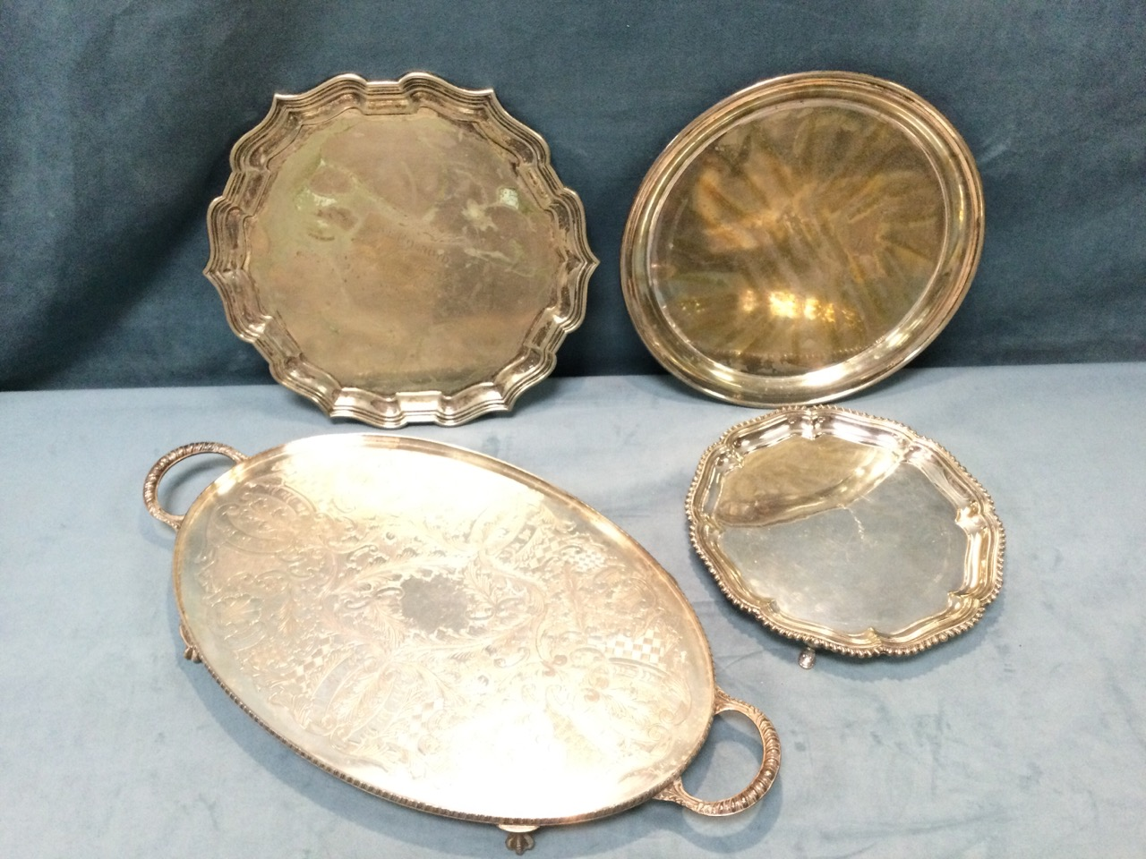A silver plated scalloped waiter with gadrooned rim on three paw feet; an oval foliate engraved tray