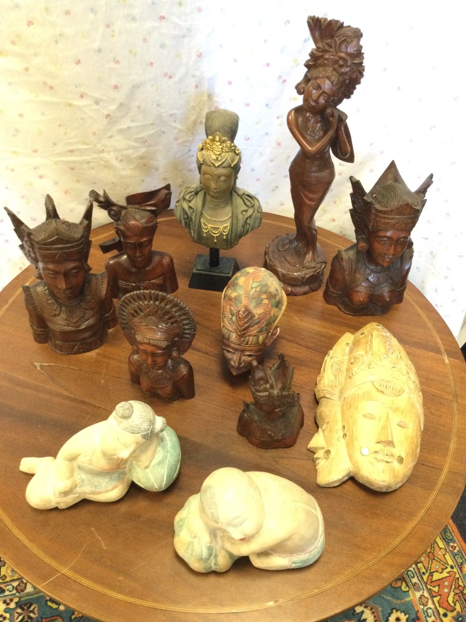 A collection of eastern carved figural wood pieces including Thai type busts, two painted sleeping