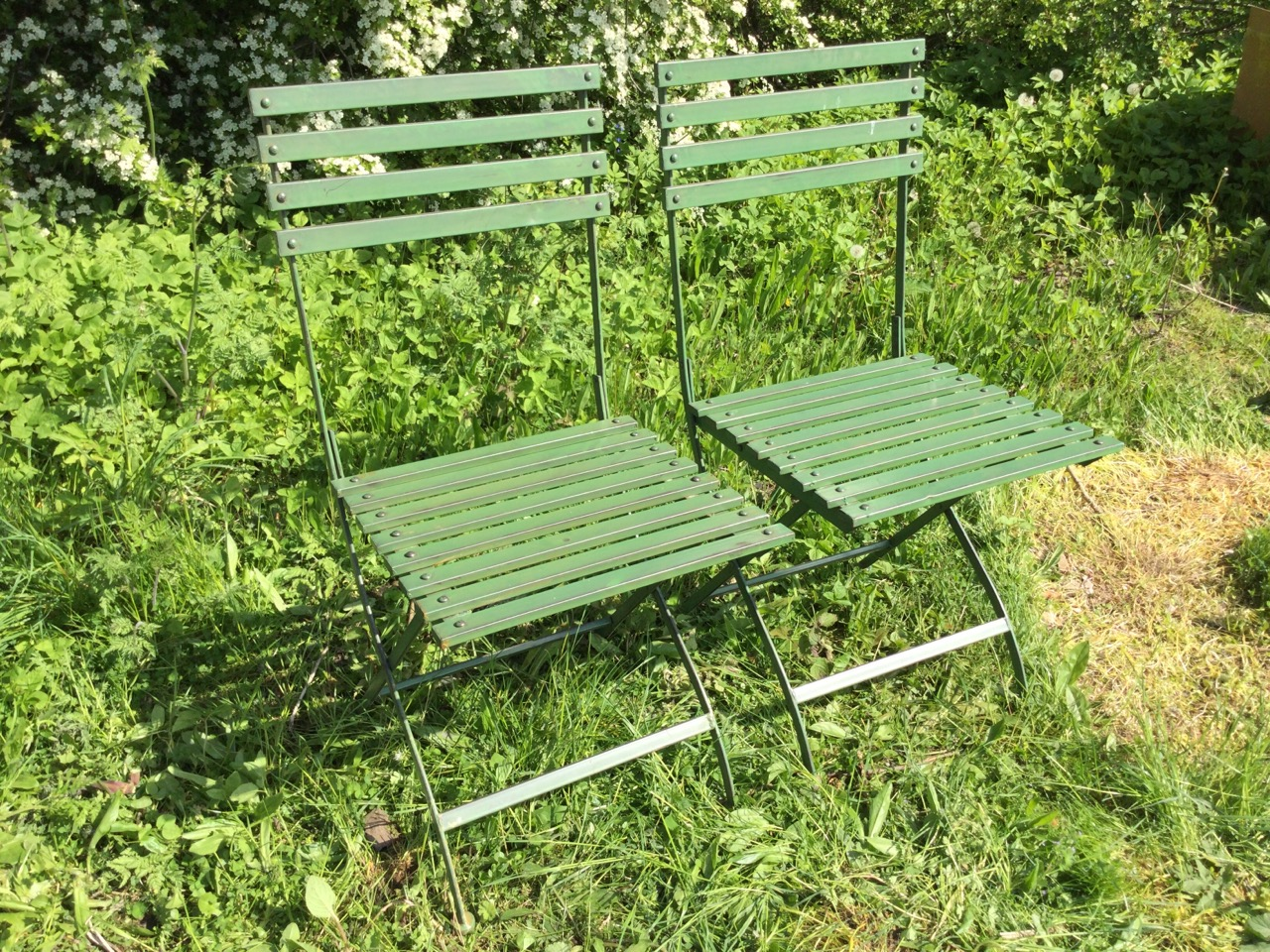 A pair of folding garden chairs with slatted backs & seats on shaped frames. (2)