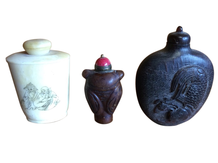 A tapering carved soapstone type snuff bottle with red ceramic stopper having brass mounts;