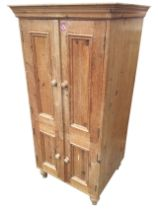 A pine cupboard with moulded cornice above four knobbed panelled doors enclosing shelves, raised